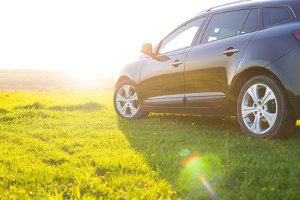The unknown vehicle car on the grass in field at summer sunset